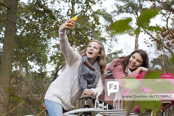 Teenage girls in forest sitting on bicycles using smartphone to take selfie smiling