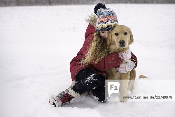 Young girl cuddling her Golden Retriever in snow