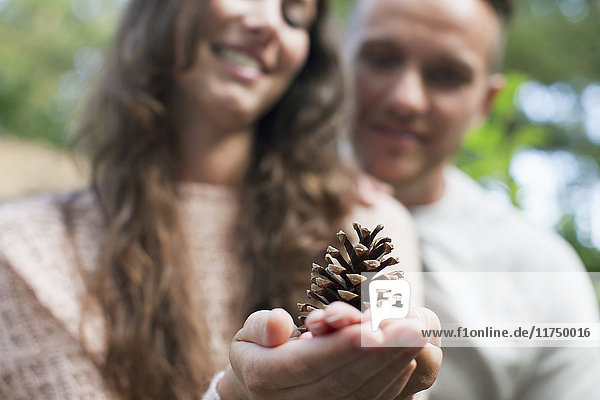 Shallow focus of couple with woman holding pine cone on hand