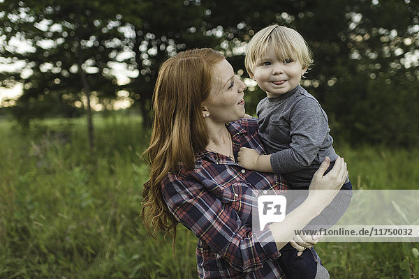 Mother holding young son in field
