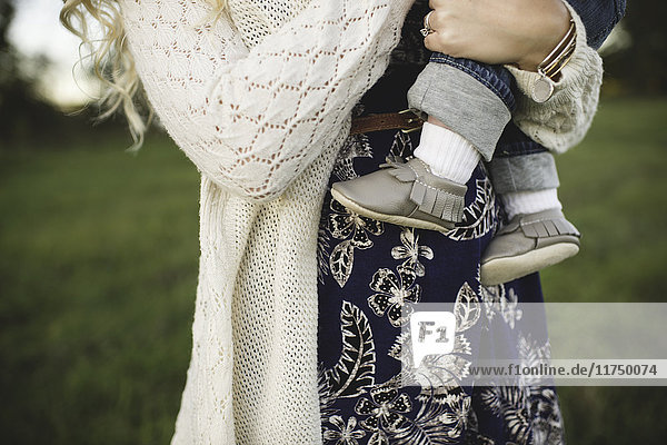 Cropped shot of baby boy in mothers arms in field
