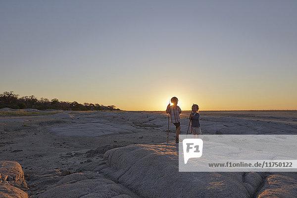 Two boys standing on rock  holding spear  sunset  Gweta  makgadikgadi  Botswana