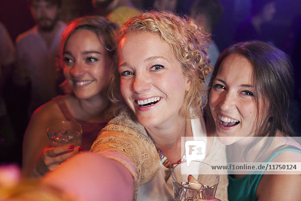 Group of young women taking selfie in club