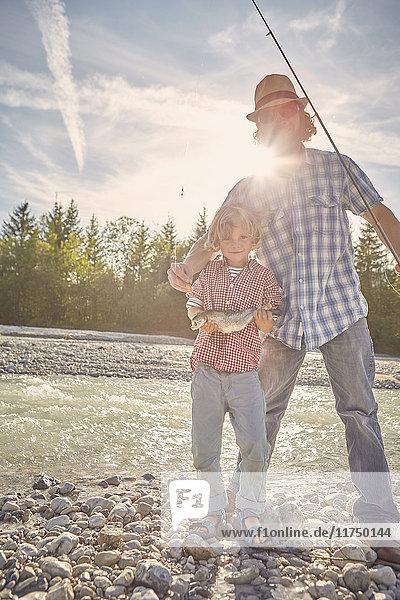 Mittelgroßer erwachsener Mann und Junge am Fluss stehend  Fische zur Schau stellend  in die Kamera blickend