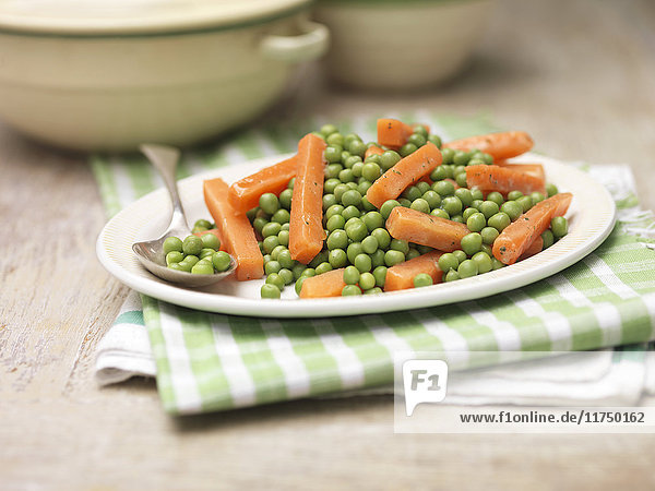 Plate of peas and carrots with mint and butter on vintage tea towel