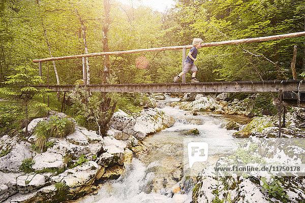 Junge läuft auf Holzsteg  Bovec  Soca  Slowenien
