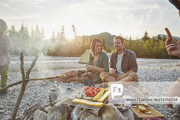Familie sitzt am Lagerfeuer und kocht Essen auf dem Grill