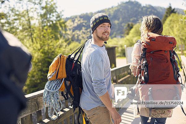 Rückansicht von Wanderern  die Rucksäcke tragen  über die Schulter schauen und lächeln