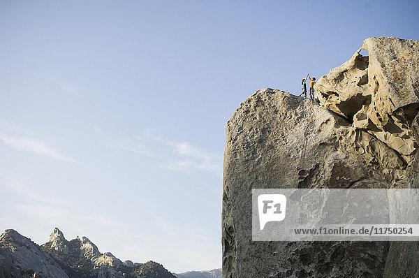 Männliche und weibliche Kletterer auf der Spitze der ''Stammesgrenzen'' 5.10a - Flaming Rock  City of Rocks  Idaho  USA