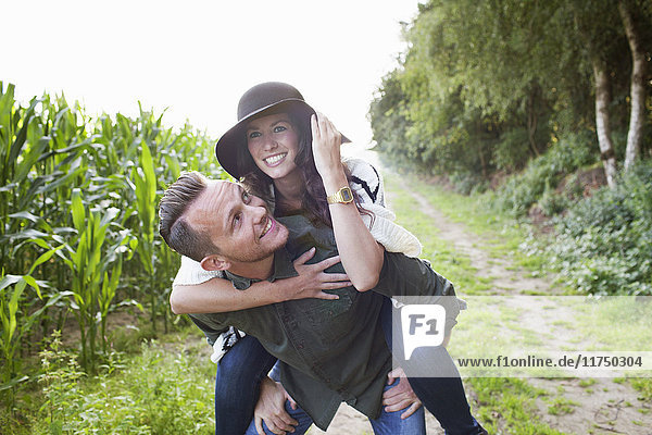 Mid adult man giving girlfriend piggy back in field