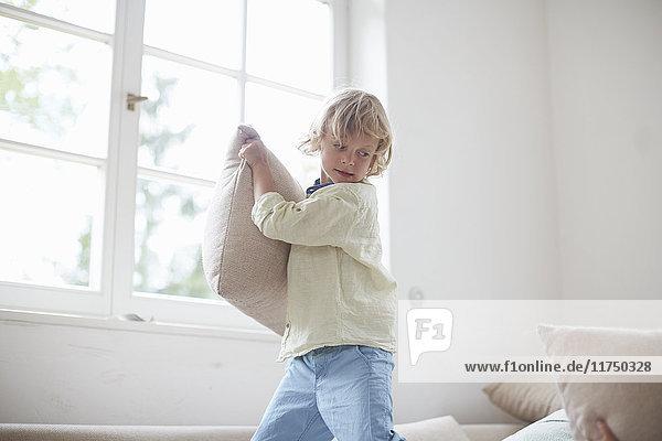 Junge hält Kissen und bereitet den Wurf vor