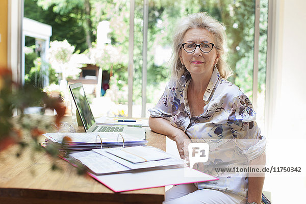 Portrait of senior woman sitting at table  with paperwork and laptop