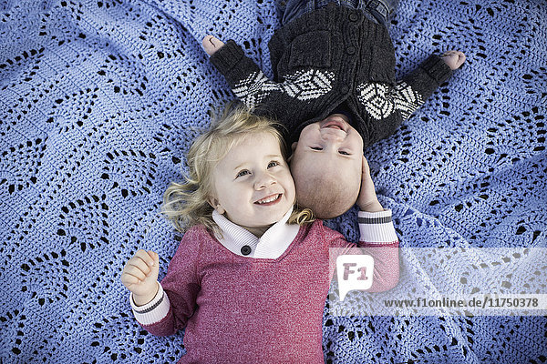 Overhead portrait of girl on blue picnic blanket with baby brother