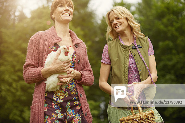 Two women in field carrying hen and basket