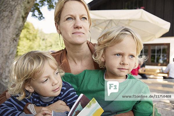 Mutter und zwei Söhne sitzen zusammen im Freien
