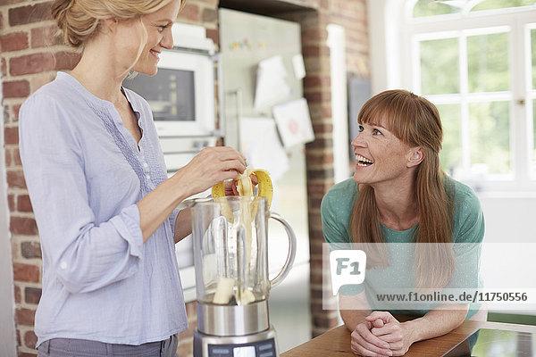 Frauen benutzen den Mixer und plaudern in der Küche