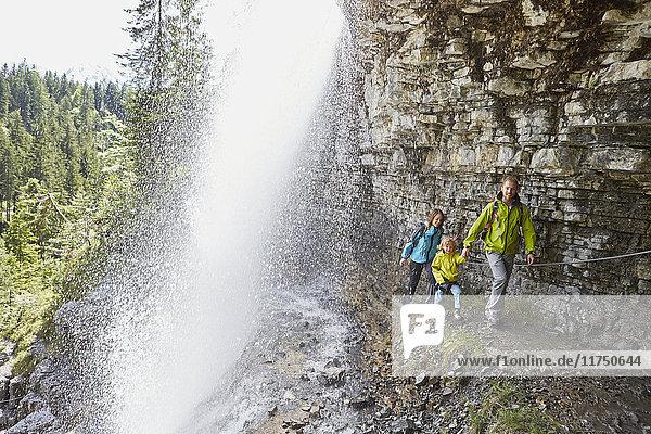 Junge Familie  zu Fuss unter einem Wasserfall