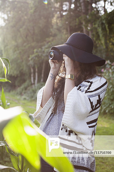 Young woman photographing in field