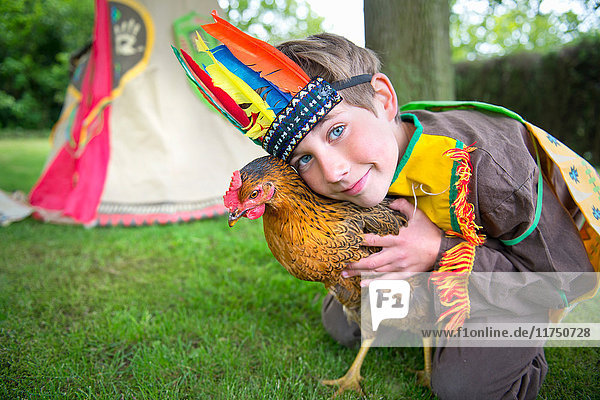 Boy dressed in Native American costume holding chicken  portrait