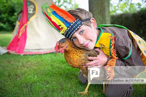 Boy dressed in Native American costume holding chicken  portrait