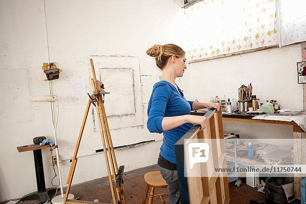 Mittlere erwachsene Frau trägt ein Ölgemälde im Atelier eines Künstlers