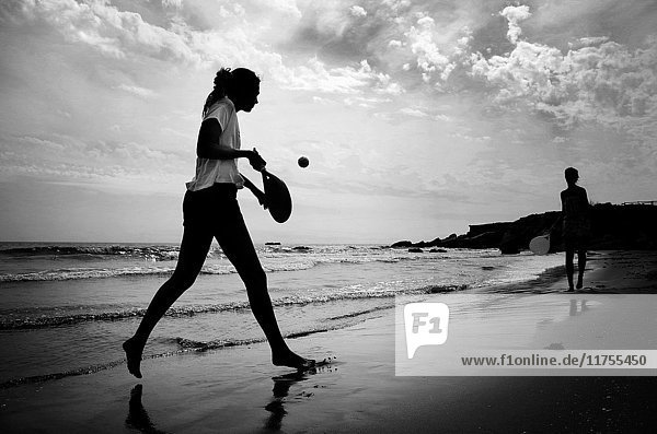 Boy and girl playing paddle beach tennis on the beach of Alcocebre  Castellon province  Valencian Community  Spain