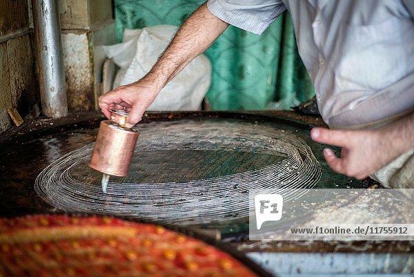 Rustam Hasanov  a baklava master  prepares the pastry at his kitchen and shop at the same time in Quba  Azerbaijan.
