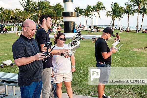 Florida  Miami Beach  Government Cut  waterfront  lawn  outdoor recreation  Hispanic  man  woman  drone operator  remote control  pilot  teacher  class
