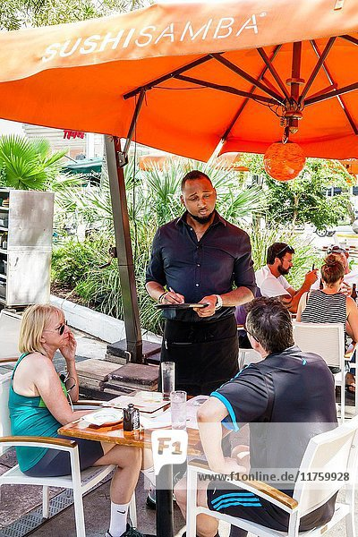 Florida  Miami Beach  Lincoln Road  pedestrian mall  Sushi Samba  Brazilian  Japanese  restaurant  outdoor  dining  al fresco  umbrella  Black  man  woman  couple  waiter  taking food order  waiter  employee