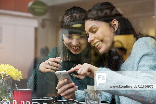 Two young women sitting in cafe window looking at smartphone