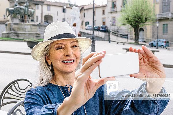 Reife Frau beim Smartphone-Selfie im Straßencafé  Fiesole  Toskana  Italien