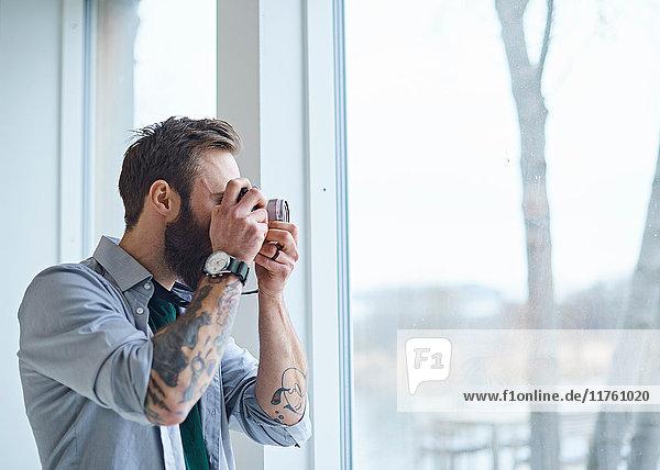 Männlicher Designer beim Fotografieren durch das Fenster des Designstudios