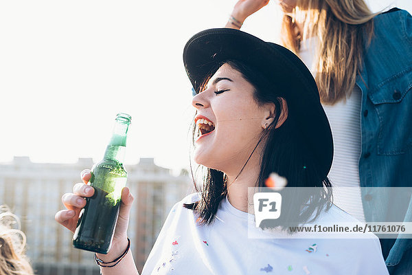 Gruppe von Freunden genießt Dachparty  junge Frau hält Bierflasche