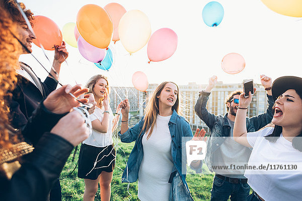 Group of friends enjoying roof party  holding helium balloons