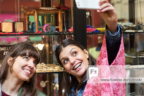 Zwei junge Frauen beim Selbstbedienungskauf im Juweliergeschäft