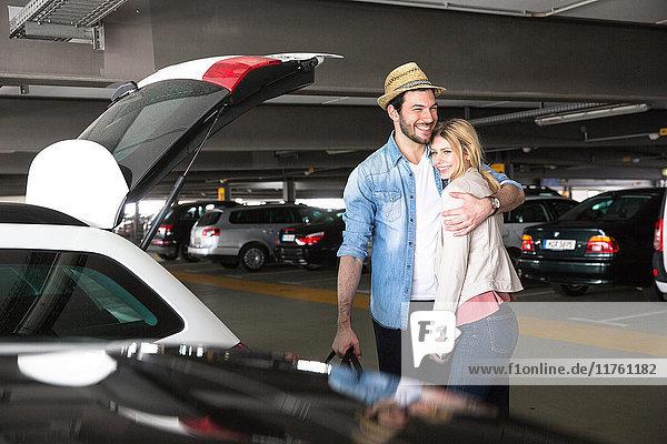 Junger Mann umarmt Freundin auf Flughafen-Parkplatz