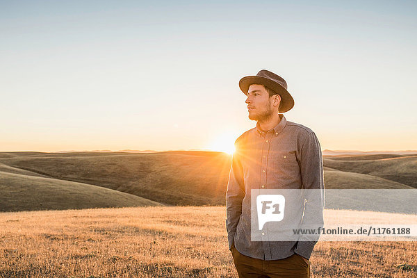 Man looking at rolling prairie hills at sunset  Bakersfield  California  USA