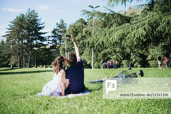 Rückansicht eines Paares  das im Park sitzend ein Smartphone mit sich führt  Arezzo  Toskana  Italien