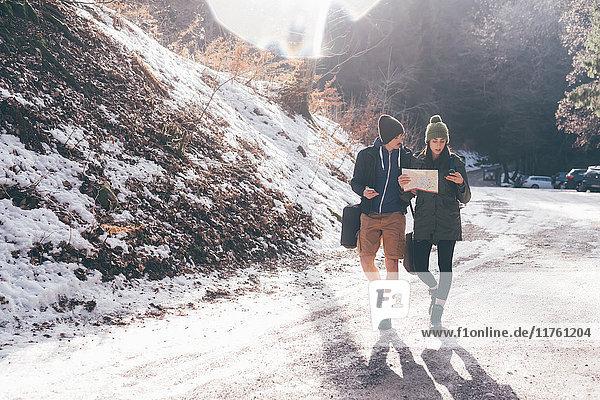 Wandererpaar betrachtet Kompasswanderung entlang der Landstraße  Monte San Primo  Italien