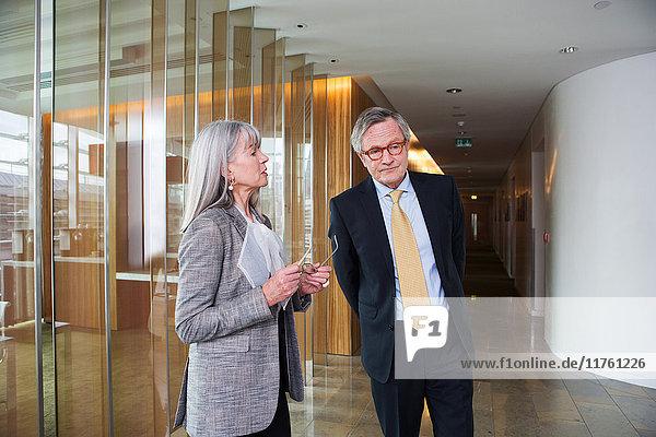 Geschäftsmann und Geschäftsfrau diskutieren im Gehen