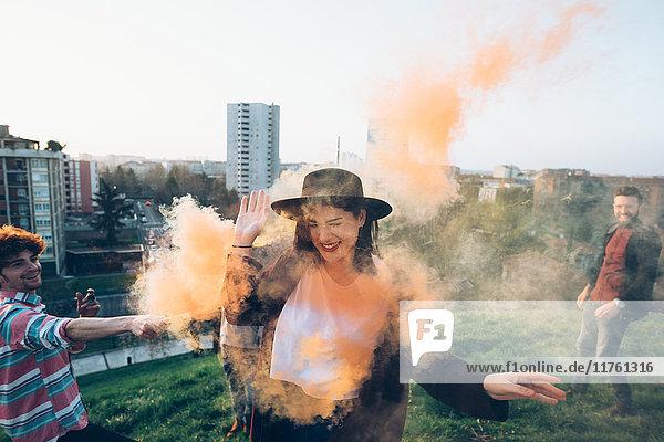Gruppe von Freunden auf dem Dach  hält bunte Rauchfackeln in der Hand  junge Frau geht durch orangefarbenen Rauch