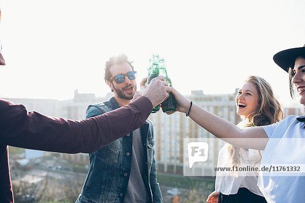 Gruppe von Freunden genießt Dachparty  hält Bierflaschen in der Hand  macht Toast