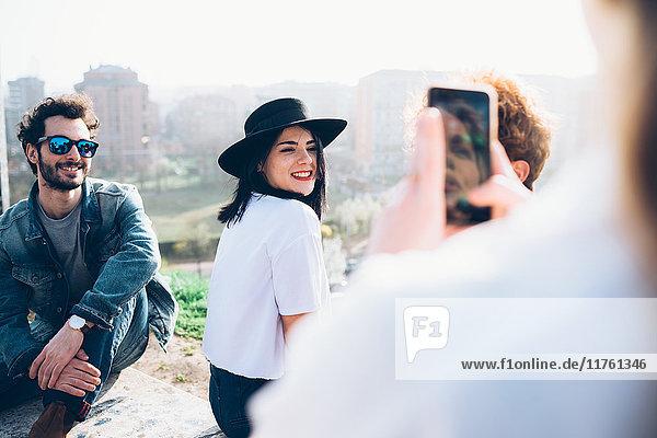 Gruppe von Freunden genießt Dachparty  junge Frau fotografiert Freunde mit Smartphone