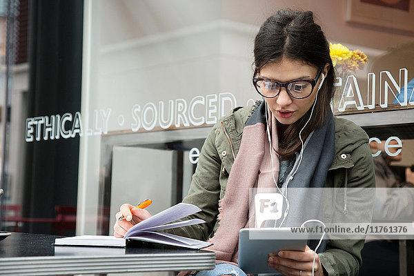 Junge Frau im Straßencafé  die auf ein digitales Tablet schaut und sich Notizen macht