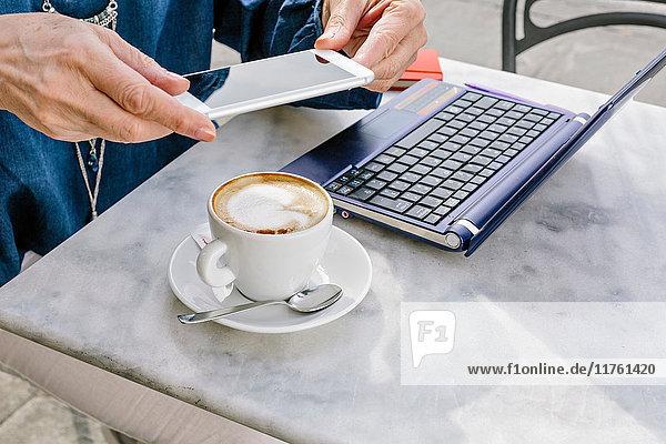 Hände einer reifen Frau mit einem Smartphone in der Hand im Strassencafé  Fiesole  Toskana  Italien