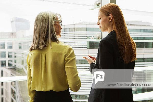 Geschäftsfrauen im Gespräch am Fenster  London  UK Geschäftsfrauen im Gespräch am Fenster, London, UK