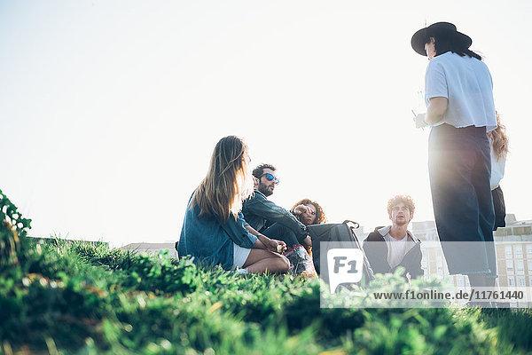 Gruppe von Freunden sitzt bei Sonnenuntergang im Dachgarten zusammen  Blick aus niedrigem Winkel