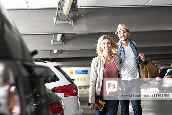 Junges Paar geht durch den Flughafenparkplatz