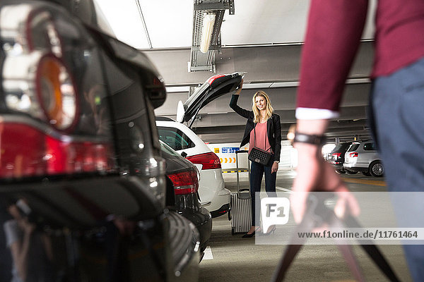 Young woman waiting for boyfriend at open car boot in airport carpark