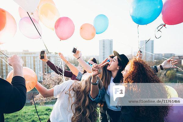 Gruppe von Freunden genießt Dachparty  hält Heliumballons